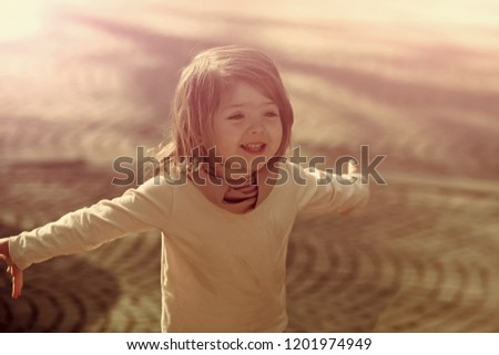 Happy girl smile with open hand gesture on sunny day on grey pavement outdoor. Child, innocence, childhood concept. #1201974949