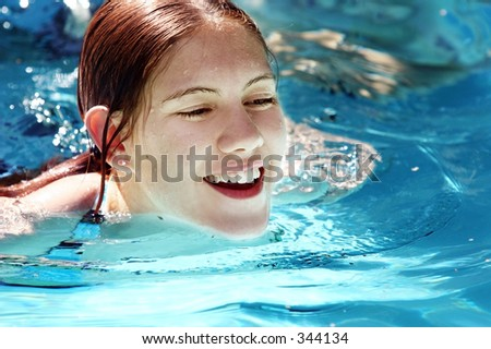 Happy girl swimming in a pool - stock photo