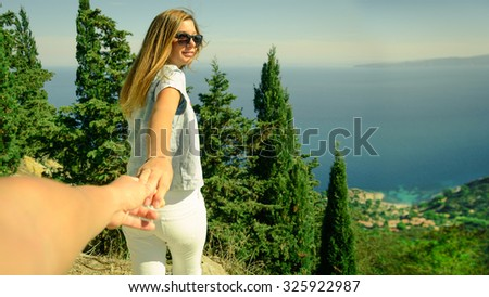 Happy girl take by hand her boyfriend to discover wild nature and seaside during their holiday - Couple hand in hand ready for adventure - Happiness, youth and travel concept, main focus on girl face