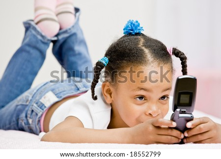 Happy girl text messaging on cell phone in bed in bedroom - stock photo