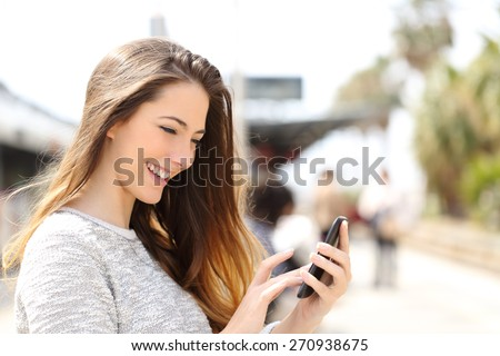 Happy girl texting on a smart phone in a train station while is waiting