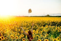 Happy Girl throwing her Hat in a Sunny Sunflower Field in Tuscany