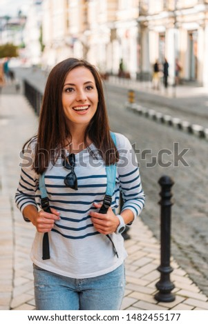 happy girl touching backpack and smiling near near building #1482455177
