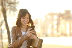 Happy girl using a smart phone in a city park sitting on a bench