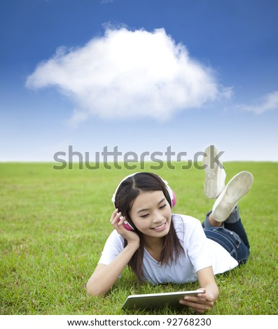 happy girl using touch pad computer with headphone on  the meadow