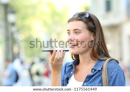 Happy girl using voice recognition of the smart phone in the street #1175561449