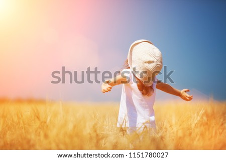 Happy girl walking in golden wheat, enjoying the life in the field. Nature beauty, blue sky and field of wheat. Family outdoor lifestyle. Freedom concept. Cute little girl in summer field #1151780027