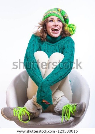 Happy girl wearing jeans, warm knitted sweater with pattern, shoes with laces and bright colorful green yellow knitted hat with big pom pon, looking up in great mood, laughing with toothy smile