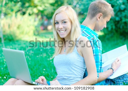Happy girl with a laptop and a student on the background at the park