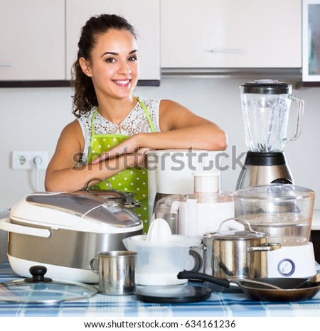 Happy girl with blender and kitchenware in domestic kitchen #634161236