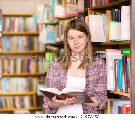 Happy girl with book at the library. looking at camera