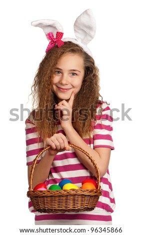 Happy girl with bunny ears, holding basket of eggs isolated on white background