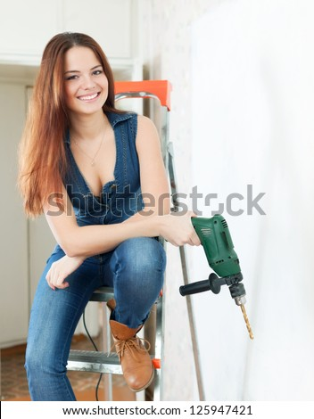 Happy girl with drill on stepladder in interior