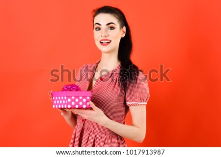 Happy girl with gift isolated on red. Girl with cheerful face, make up and pink pack. Woman in stylish dress holds present. #1017913987