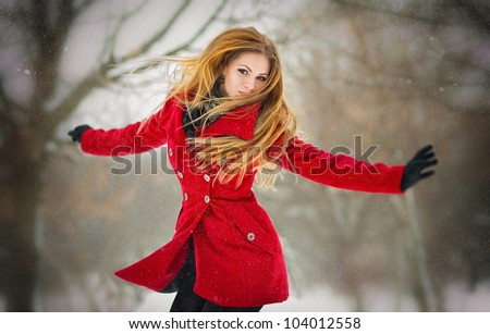 Happy girl with  gloves playing with snow and jump  in the winter landscape