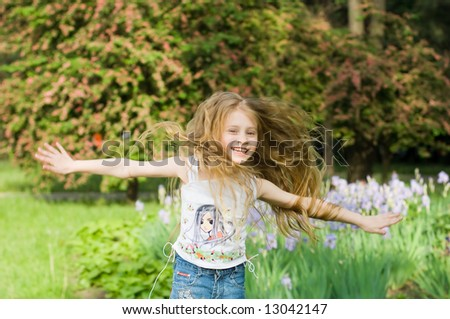 Happy girl with hands open, with trees and flowers on background