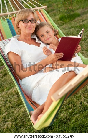 Happy girl with mother reading a book in colorful hammock