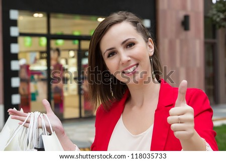 Happy girl with thumb up show approved sign by hand in the city. Beautiful young woman holding shopping bags, showing the sign OK and smiling to camera in front of store