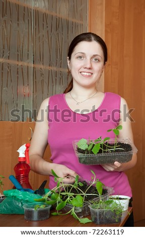 Happy girl with various seedlings at home