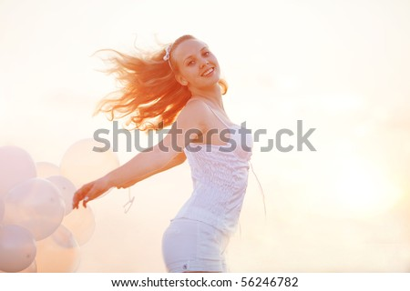Happy girl with white air balloons in evening sunshine