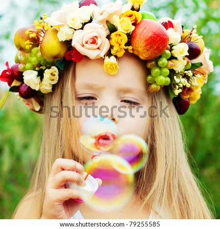 Happy Girl with Wreath from Flowers blows Soap Bubbles at Summer. Happy Children. - stock photo