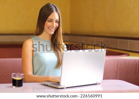 Happy girl working with a laptop in a restaurant interior
