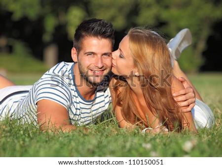 Happy girlfriend kissing her friend outdoor