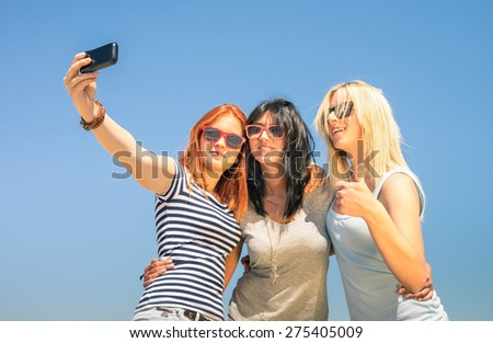 Happy girlfriends taking selfie against blue sky - Friendship summer concept with new trends and technology - Best friends enjoying moments with modern smartphone - Warm sunny afternoon color tones