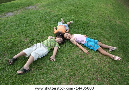 Happy girls and boy lying on the grass