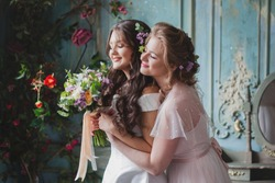 Happy girls at their best friend's wedding. Beautiful and elegant bride with her friends. Beautiful young women in wedding dresses with flowers. Wedding celebration