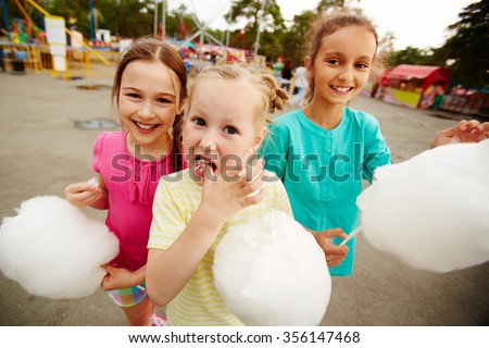 Happy girls eating cotton candy in the park #356147468