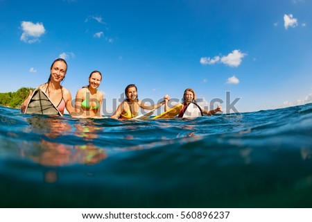 Happy girls in bikini have fun - group of surfers sit on surf boards, young women wait for big ocean wave. People in water sport adventure camp, beach extreme activity on summer beach family vacation.