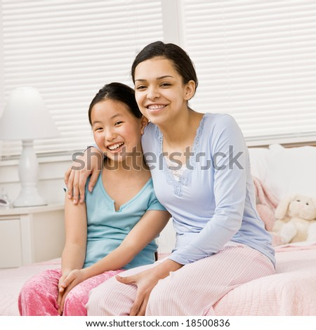 Happy girls in pajamas hugging in bedroom