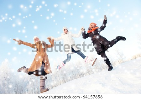 Happy girls jumping in the snow