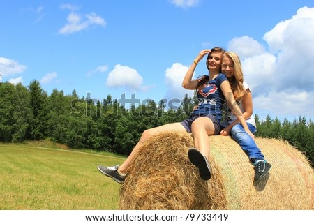 Happy girls on fresh hay at field