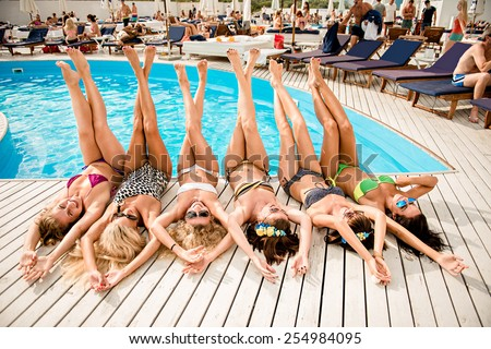 happy girls on the beach. beautiful girlfriends lie on white wooden floor near the pool. girls lying on their backs #254984095