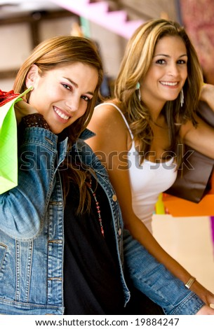 happy girls or women smiling and carrying shopping bags in a store