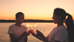 Happy girls set fire to sparklers at sunset in the sky and laugh. Young people greet the sunrise with beautiful lights. Girlfriends travel. Rest during the holidays. Celebrating birthday with fun