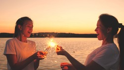Happy girls set fire to sparklers at sunset in the sky and laugh. Young people greet the sunrise with beautiful lights. Girlfriends travel. Rest during the holidays. Celebrating your birthday with fun