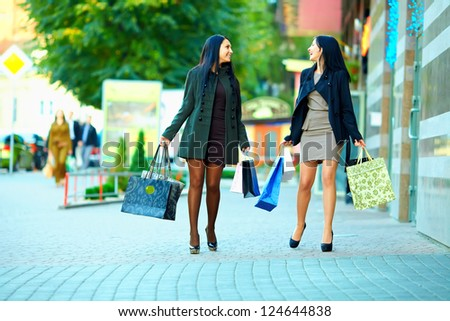 happy girls shopping on crowded city street