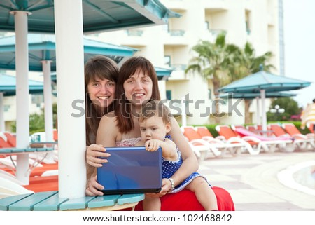 happy girls   sitting  with laptop at resort beach