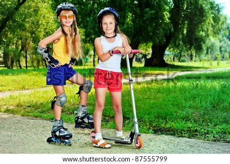 Happy girls with roller and scooter in a summer park.