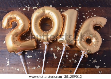 Happy 2016 gold New Year Balloons with glitter stars on dark wood table background.