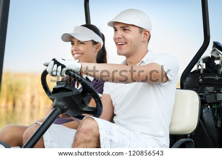 Happy golf couple driving golf cart