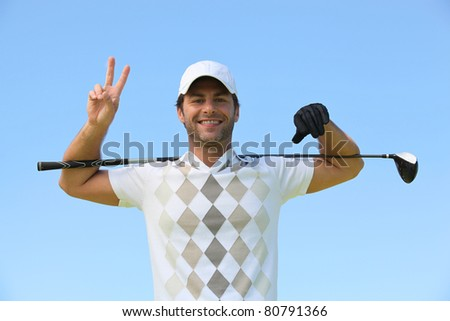 Happy golfer giving peace sign
