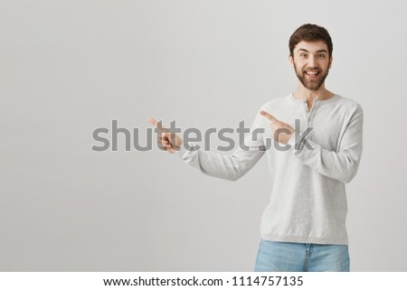 Happy good-looking caucasian bearded guy pointing left with both index fingers, smiling and being excited while standing over gray background. Upbeat boyfriend asks permission to ride roller coaster