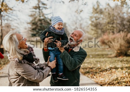 Happy good looking senior couple husband and wife walking and playing with their adorable grandson in public city park