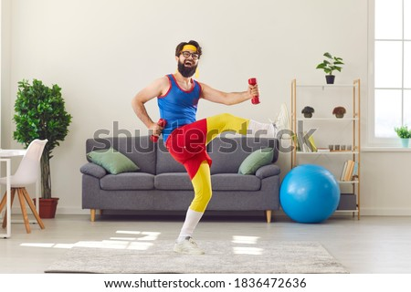 Happy goofy young man in retro sportswear decided to start fitness training and now is exercising with dumbbells and laughing, motivating you to do sports, keep fit and lead healthy lifestyle too Foto stock ©