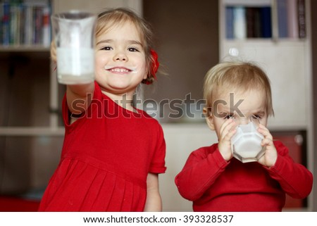 Happy gorgeous little girl with milk mustache showing an empty glass while her little cute brother drinking a glass of milk at home, food and drink concept, healthy food, indoor