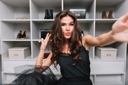 Happy gorgeous young woman with curly brown hair, dancing and taking selfie in her dressing room. She showing kiss to camera. She enjoying good day. Wearing black dress.